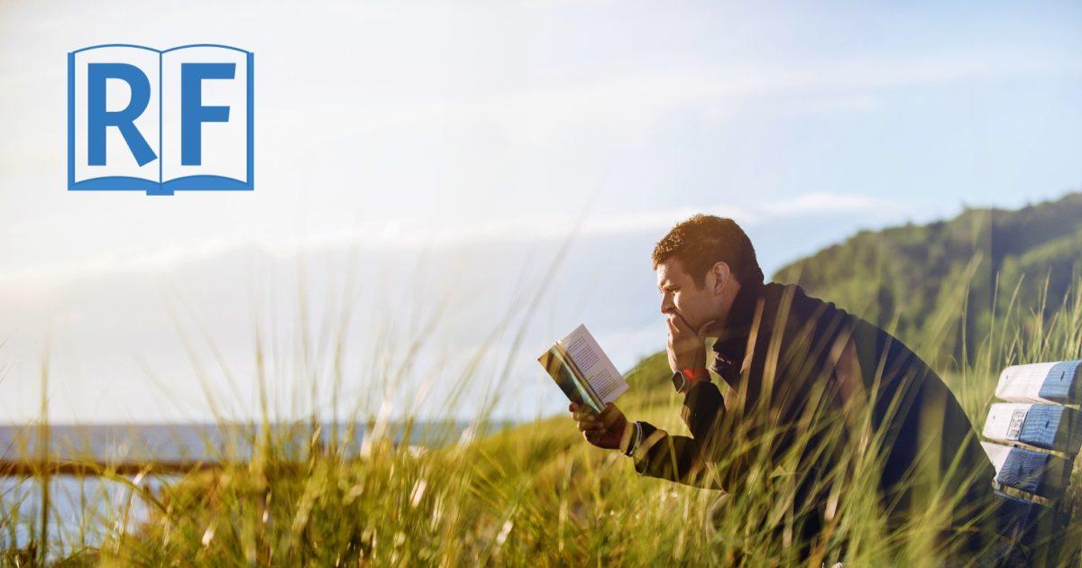 Person reading suttas outside sitting near a lake
