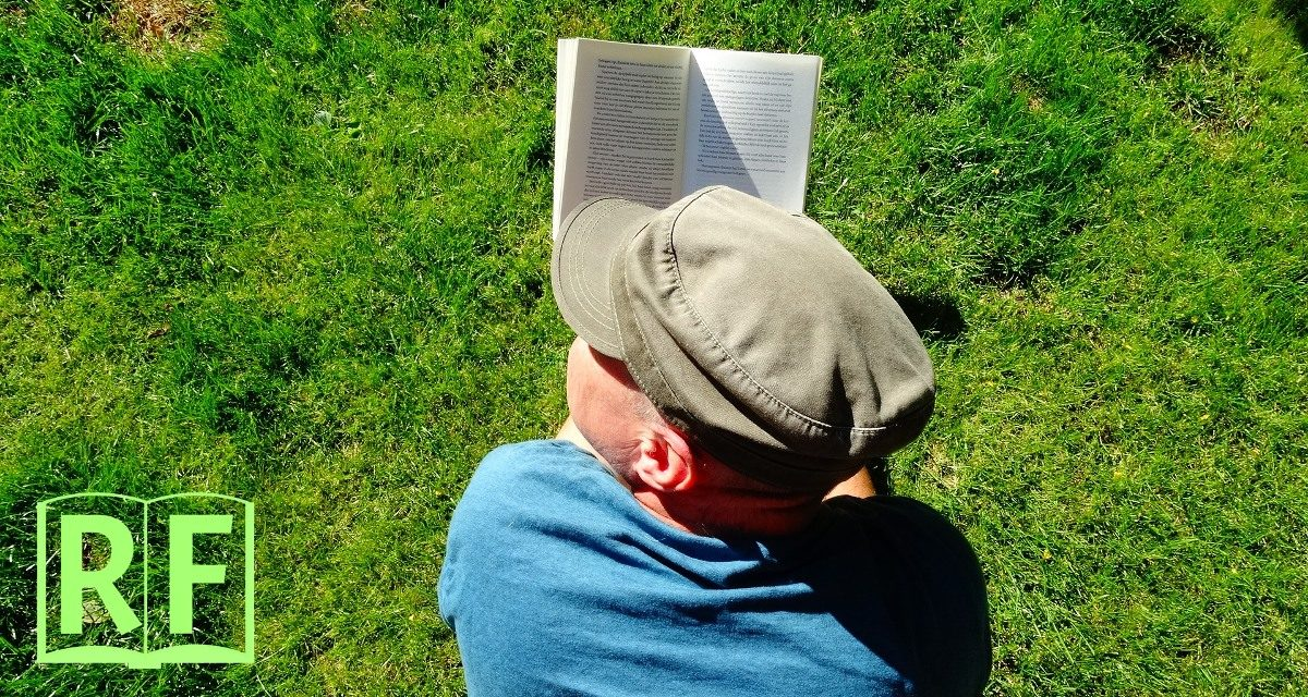 Person lying on the grass reading their backup sutta text